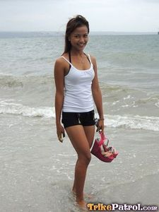 Cute asian teen in short-shorts on the beach.